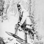 Photograph, taken in a studio in front of a winter woodland scene, of a man in winter clothing and snowshoes, 1869