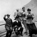 Black and white photograph of four men and a woman, holding cameras, at the bow of a steamship