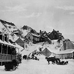 Photograph showing houses in a hillside in winter, with horses and sleighs outside, Lévis, Quebec, circa 1870-1875