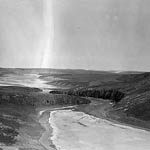 Photograph of the partially frozen Coppermine River, with a sun dog in the sky above, Northwest Territories, date unknown