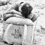 Photograph of a young Korean boy resting his head and shoulders on top of a ration box, Korea, 1951