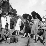 Photograph of a group of eight people, mostly women, some with parasols, posing for a picture during a hike along a railroad track, near Montfort, Quebec, 1928