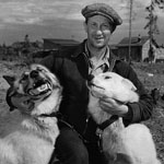 Black and white photograph of a man patting two husky dogs