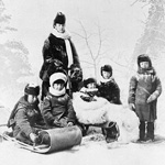 Photograph of the Countess of Dufferin and her children in winter clothes posed before a winter background in a studio, 1873