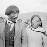 Photograph of an Inuit couple, with other Inuit in the background, Northwest Territories, circa 1920s