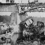 Photograph of a locomotive that fell from a bridge, with men looking on from the bridge above, Bel�il, Quebec, 1864