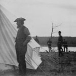 Photograph of a bearded Louis Riel standing outside a tent while soldiers look on, Batoche, Saskatchewan, 1885