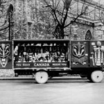 Photograph of a display, on wheels, of Canadian icons such as wheat and wolves, reading YOU NEED CANADA NEEDS YOU, London, England, date unknown