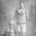 Photograph of Tom Longboat with several of his trophies, 1907