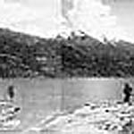 Panoramic photograph of the city of Kaslo, British Columbia, beside a body of water, with mountains in the background, 1899