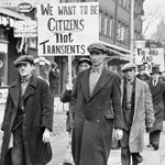 Photograph of a group of men, some carrying signs, from the Single Men's Unemployed Association marching to Bathurst Street United Church, Toronto, circa 1930