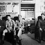 Photograph showing four men in military uniform waiting their turn outside an office, Toronto, 1944