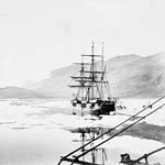 Photograph of a sailing ship, the ALERT, navigating along a thin stretch of open water, almost completely surrounded by ice, Dobbin Bay, Northwest Territories, 1875
