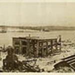 Photograph showing wrecked and burned-out buildings, railway tracks and ships along the Halifax shoreline and up the hill, Halifax, Nova Scotia, 1917