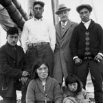 Photograph of four men, a women and a young girl on board a sailboat, Aklavik, Northwest Territories, date unknown