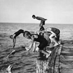 Black and white photograph of seven boys diving off a pier