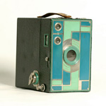 Photograph of a box camera with a two-tone green faceplate and a matching leatherette exterior