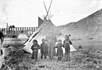 Photograph of a Native woman and four children, standing in front of a teepee