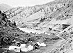 Photograph showing tents from an Native camp at Thompson River, British Columbia, with the Canadian Pacific Railway tracks in the background, c. 1899